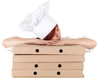 Tired female cook sleeping on boxes of pizza Stock Photo