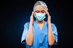 Tired female doctor in medical mask and cap has a headache isolated Stock Photo