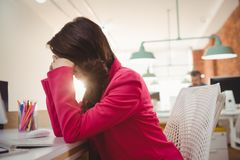 Tired female executive sitting with hands on forehead at desk Stock Image