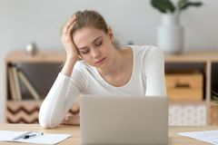 Tired female fall asleep near laptop at home desk royalty free stock image
