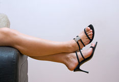 Tired female feet in snadals over couch Royalty Free Stock Photos