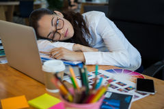 Tired female graphic designer sleeping at desk. In office royalty free stock images