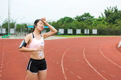 Tired female jogger at the running track. On a warm day stock photo
