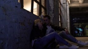 Tired female and male sitting near wall and talking, after-party in night club. Stock footage stock footage