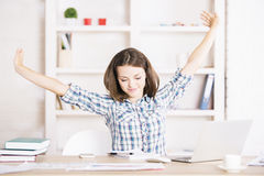 Tired female in office stretching arms Royalty Free Stock Image
