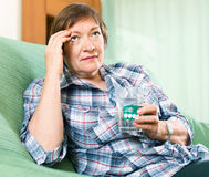 Tired female pensioner with pills and glass of water Stock Photos