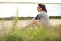 Tired Female Runner Sitting on Grass Stock Photos
