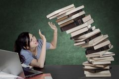 Tired female student holds falling books. Image of female college student looks tired while holding a pile of falling books and sitting in the classroom royalty free stock photo