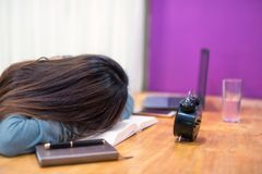 Tired female student sleep on book. Tired student woman in house sleep on text book above working table. Serious exhauasted Asian girl wok hard by reading book Stock Photography