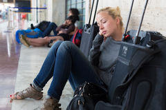 Tired female traveler waiting for departure. Royalty Free Stock Images