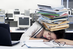 Tired female worker with paperwork on desk Stock Photo
