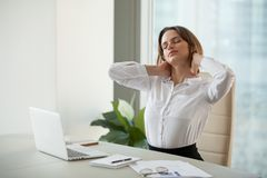 Tired female worker stretching in chair relaxing after working d royalty free stock images