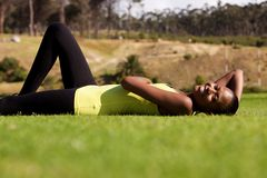 Tired fit woman relaxing at park Stock Image