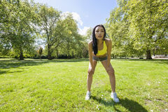 Tired fit woman taking a break while exercising in park Stock Photos