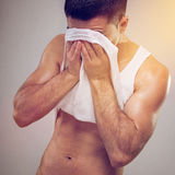 Tired fit young man wiping sweat off his face Royalty Free Stock Photos