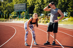 Tired fitness couple of runners at the stadium Royalty Free Stock Images