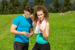 Tired fitness couple of runners sweating and taking a rest during training in country road. Tired fitness couple of runners sweating and taking a rest during Royalty Free Stock Photo