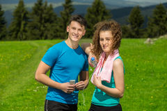 Tired fitness couple of runners sweating and taking a rest during training in country road. Tired fitness couple of runners sweating and taking a rest during Royalty Free Stock Images