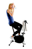 Tired fitness girl. Tired girl drinking mineral water during exercising on stationary training bike - isolated on white background Stock Image