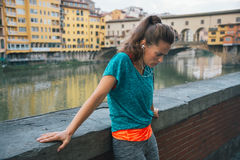 Tired fitness woman in front of ponte vecchio in florence, italy Royalty Free Stock Image