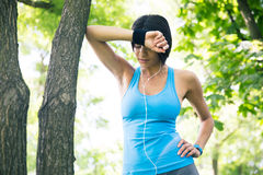 Tired fitness woman resting outdoors Royalty Free Stock Image
