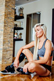 Tired fitness woman resting and thinking while sitting on the fl Royalty Free Stock Image