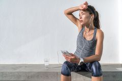 Tired fitness woman sweating listening to music. Tired fitness woman sweating taking a break listening to music on phone after difficult training. Exhausted royalty free stock photos