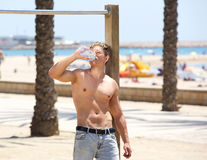 Tired fitness young man drinking water after workout Stock Images