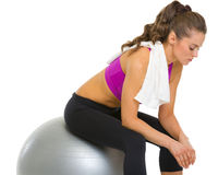 Tired fitness young woman sitting on fitness ball Royalty Free Stock Photos