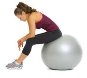 Tired fitness young woman sitting on fitness ball Stock Images