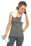 Tired fitness young woman with towel and bottle of water Stock Photography