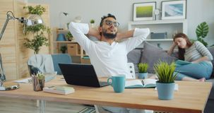 Tired freelancer working with laptop relaxing while woman reading in background. Tired freelancer handsome Arabian man is working with laptop then relaxing stock footage