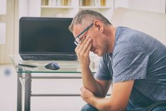 Tired freelancer man rubbing his eyes Royalty Free Stock Photos