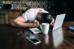 tired freelancer remote working lying on table with laptop calculator and cup of coffee in kitchen royalty free stock image