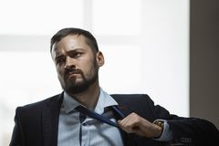 Tired Businessman After Work. Tired, frustrated handsome man looking exhausted while standing against a window in the office. Brutal angry businessman with a stock images