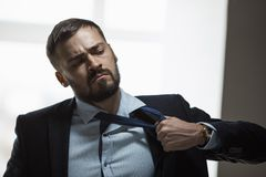 Tired Businessman After Work. Tired, frustrated handsome man looking exhausted while standing against a window in the office. Brutal angry businessman with a royalty free stock photo