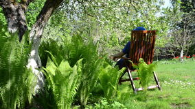 Tired gardener sits on a chair Royalty Free Stock Photo