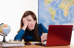 Tired geography teacher at a laptop Royalty Free Stock Image