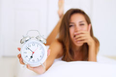 Tired girl with an alarm clock Royalty Free Stock Photo