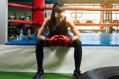 Tired girl athlete sitting in the boxing ring. beautiful woman holds hands in boxing gloves. stock photos