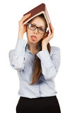 Tired girl with book over her head Royalty Free Stock Photos