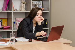 Tired girl at the computer prints document Royalty Free Stock Image