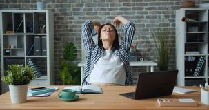 Tired girl working with laptop in office then stretching arms relaxing at work stock video
