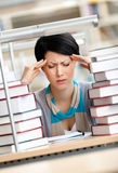 Tired girl with headache sitting at the desk. Surrounded with piles of books Stock Photos