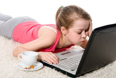 Tired girl with a laptop and a coffee cup Royalty Free Stock Images
