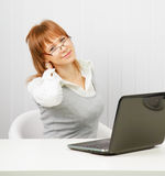 Tired girl with a laptop stretches Royalty Free Stock Photos