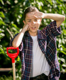 Tired girl leaning on shovel after work at garden Royalty Free Stock Photography