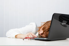 Tired girl lies on a table Royalty Free Stock Image