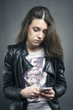 Tired girl looking at phone with bored emotion on her face Royalty Free Stock Photography