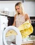 Tired girl near washing machine Royalty Free Stock Image